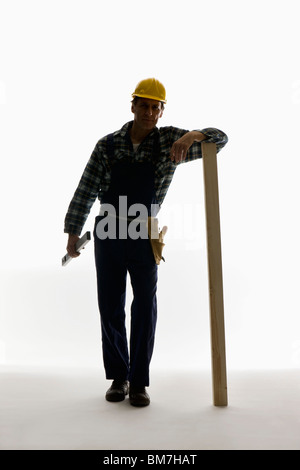 A construction worker carrying a level and leaning on a plank - Stock Photo