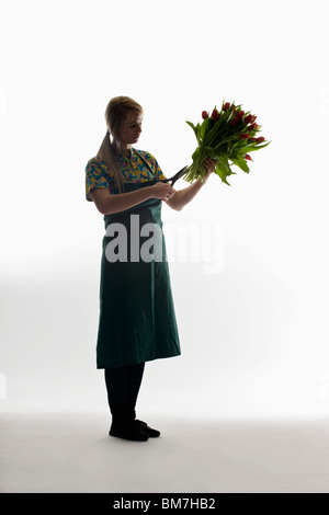 A florist trimming the stems of a bunch of tulips - Stock Photo