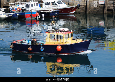 a fishing boat leaving the harbour at brixham in devon, uk - Stock Photo