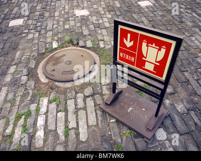 Red sign in Chinese pointing at the fire hydrant under sewer manhole on the Forbidden City territory in Beijing, - Stock Photo