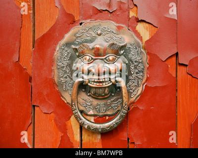 Door knocker on an old red door at hutongs in Beijing, China - Stock Photo
