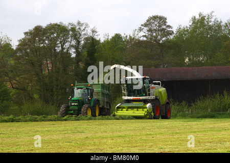 Claas Jaguar 950 with 300 pickup attached and John Deers 7930 Tractor - Stock Photo