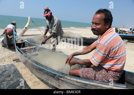Fishermen working on Marari Beach or Secret Beach near the town of Alleppey in Kerala, India. - Stock Photo