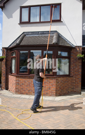 North Wales UK Self employed windown cleaner man using a pure water fed pole window cleaning system with no need - Stock Photo