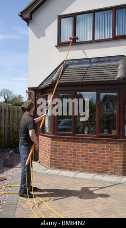 North Wales UK Self employed window cleaner man using a pure water fed pole window cleaning system with no need - Stock Photo