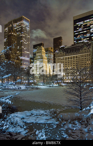 Manhattan skyline including the Plaza Hotel & GM Building at night as seen from Gapstow Bridge in Central Park after - Stock Photo
