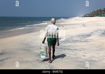 Fishermen working on Marari Beach or Secret Beach near the town of Alleppey in Kerala, India. - Stock Photo