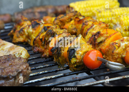 Pork kebabs cooking on a barbecue - Stock Photo