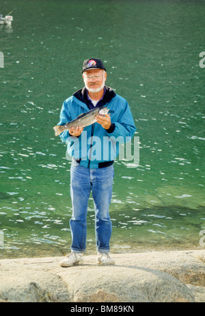 Man holds seven pound rainbow trout caught in South Lake, Eastern Sierra, near Bishop, CA, USA - Stock Photo