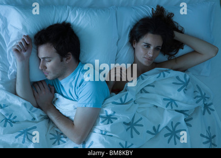 Couple lying together in bed, woman restlessly awake looking away - Stock Photo