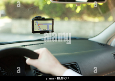 Driver using GPS unit for navigation assistance - Stock Photo