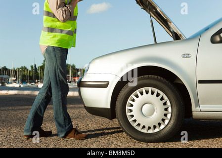Mechanic evaluating car breakdown on side of road - Stock Photo