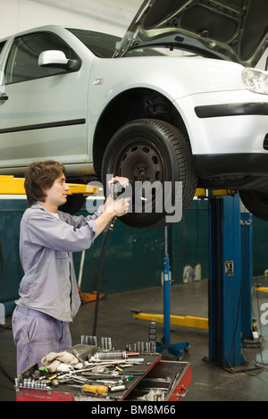 Mechanic changing tires of car elevated on hydraulic lift - Stock Photo