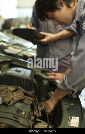Mechanics repairing car engine - Stock Photo
