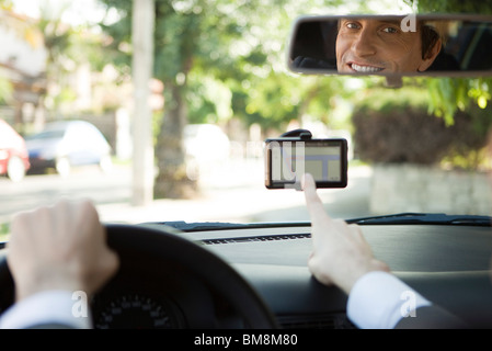 Driver using GPS for navigation assistance - Stock Photo