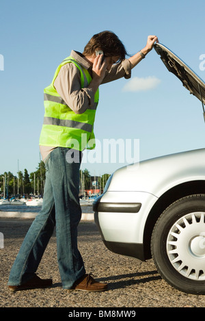 Man making phone call with cell phone while evaluating car broken down on side of road - Stock Photo