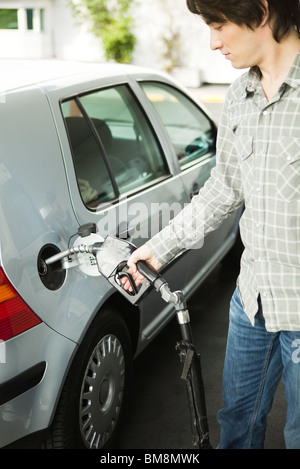 Man refueling car at gas station - Stock Photo