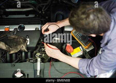Mechanic diagnosing car engine problem - Stock Photo