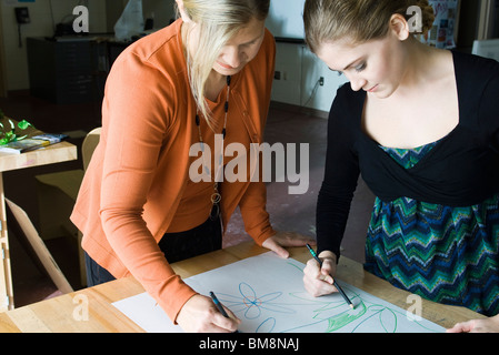 Female artists collaborating on drawing - Stock Photo