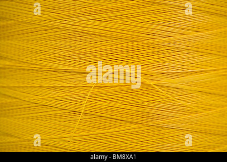 Fabric coating plant, recyclable composite textile weaving department, close-up of reel of coated thread - Stock Photo