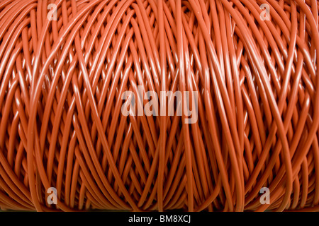 Fabric coating plant, recyclable composite textile weaving, close-up of reel of coated thread - Stock Photo