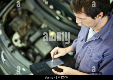 Mechanic using electronic tools to evaluate car performance - Stock Photo