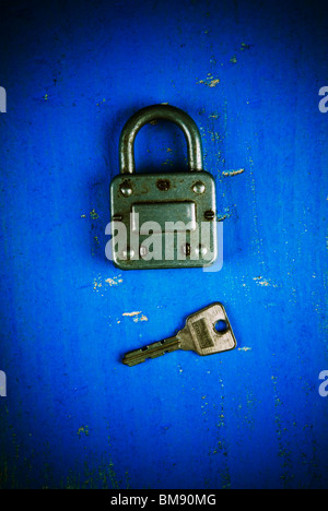 Old fashioned padlock with key on a blue wooden background - Stock Photo