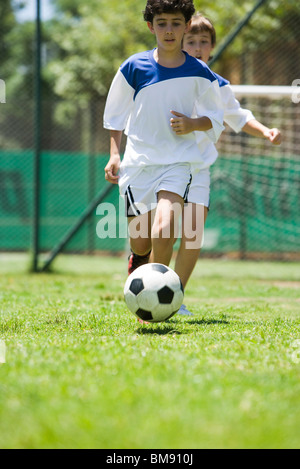 Children playing soccer, cropped - Stock Photo