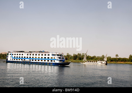 Egypt, cruising on the Nile.  Contrast between dahabiya, small restored sailing boat (1920s-1940s) and mass tourism - Stock Photo