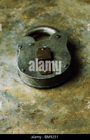 Old fashioned rusty padlock over a grungy background - Stock Photo