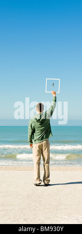 Man on beach holding up picture frame capturing image of gull flying against blue sky - Stock Photo