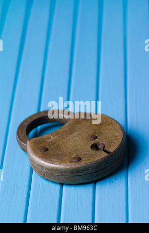 Old fashioned padlock on a blue wooden background - Stock Photo
