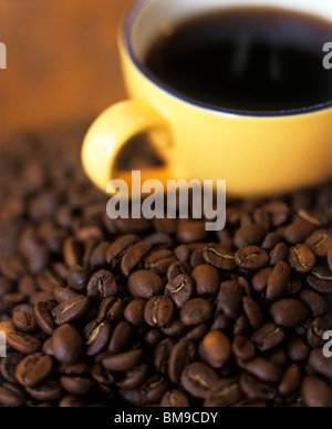 Coffee Cup in mound of coffee beans - Stock Photo