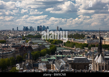 Aerial city view of Paris rooftops and Seine from Ile De la Cite toward the Grand Arch, dramatic blue sky and cloud - Stock Photo