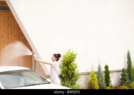 Young woman washing car, holding hose - Stock Photo