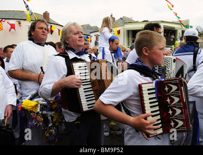 followers of the blue oss marching through the streets of padstow, cornwall on obby oss day - Stock Photo
