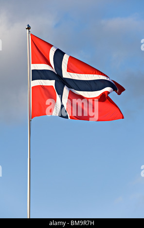 Norwegian Flag Flies Proudly in a Breeze from a Flagpole in a Clear Blue Sky - Stock Photo