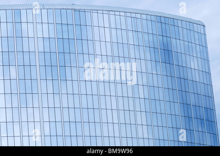 Glass wall of business center and sky reflection - Stock Photo