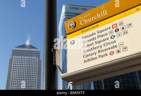 Close up of pedestrian direction sign with view of Canary Wharf tower behind, London's Docklands, London, UK. - Stock Photo