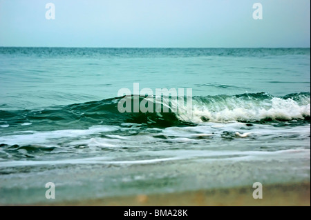 Shot at a low wide angle as a wave is rolling across the scene, breaking from right to left. - Stock Photo