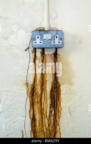 Rust seeping from electrical power point,abstract,electricity prices, health and safety,HSE,IOSH,EOSH,leaking power - Stock Photo