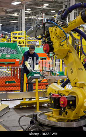 Robot and Worker on Assembly Line at Chrysler Plant - Stock Photo
