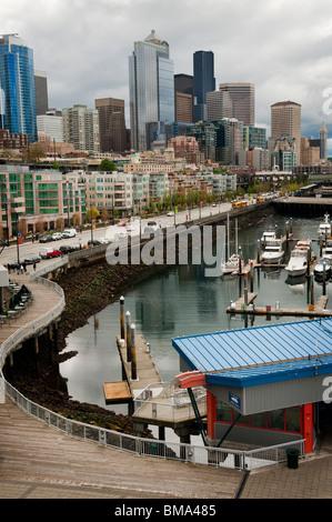 The dramatic Seattle, Washington skyline as seen from pier 66 on the Elliott Bay waterfront. Marinas, restaurants - Stock Photo
