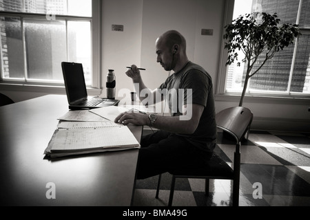 Balding young man working on his laptop computer in the dining area at his college. - Stock Photo