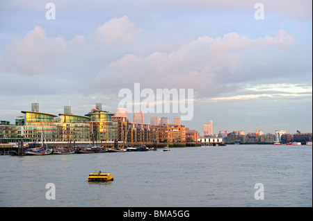 Typical luxury Thames riverside development, Wapping, East End, London, England, UK, with Canary Wharf in the background - Stock Photo