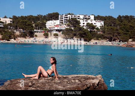 A sunbather enjoys the views of the beach at Portinatx on the island of Ibiza. - Stock Photo