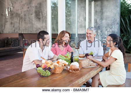 Adult family members at table outdoors - Stock Photo