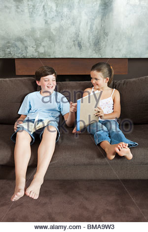 Boy looking at a picture his sister has drawn - Stock Photo