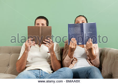Young couple peeking over books - Stock Photo