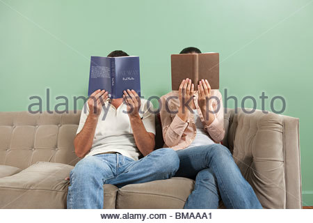 Young couple reading with books obscuring faces - Stock Photo